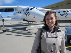 SpaceKate standing in front of Virgin Galactic's White Knight and Spaceship 2